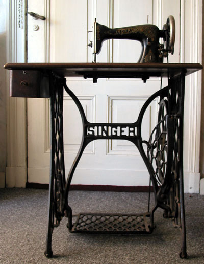 Typical Singer treadle sewing machine in table with iron stand.