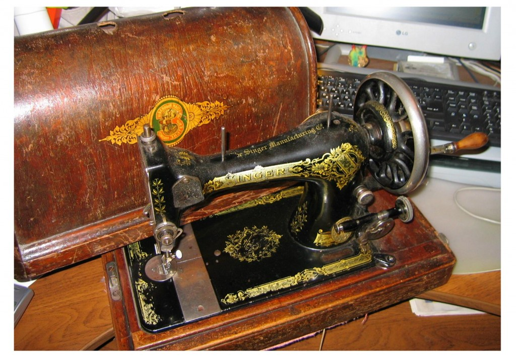 "Hand-operated Singer sewing machine.  ""Singer"" on the wooden case is printed in the Cyrillic alphabet, while the machine itself is not."
