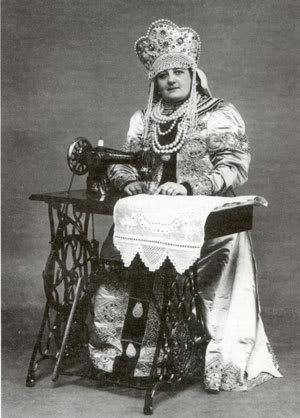 Singer ads portrayed women of many countries sewing at their machines.  This is a woman in traditional Russian costume, including a headdress in reality far too heavy to allow bending over her work.